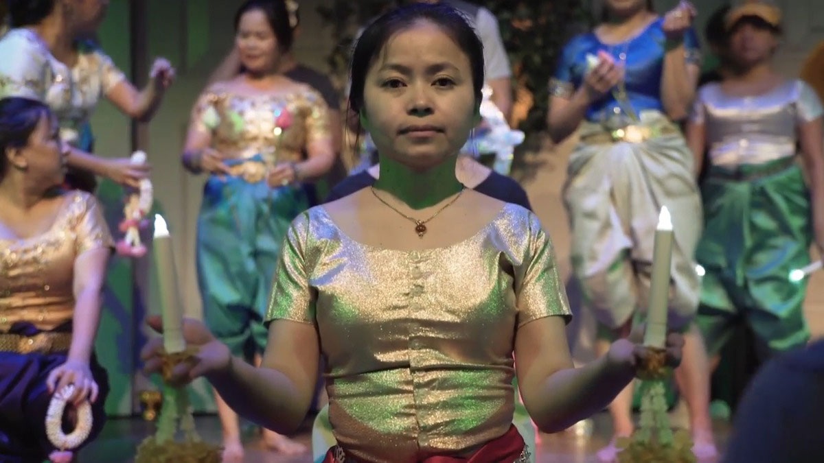Dancers on stage in shimmering green, white, and gold costumes. A woman in front looks straight into the camera, holding a battery-powered candle in each hand.