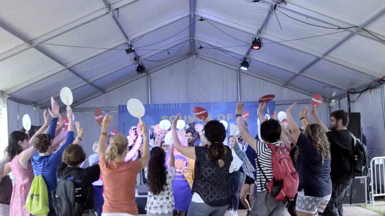 A crowd of people dance in a circle, raising up their hands and red paper fans under a festival tent.