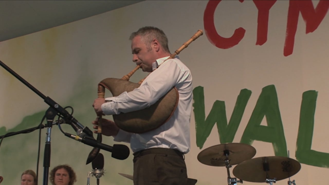 A man plays a bagpipe on a stage.
