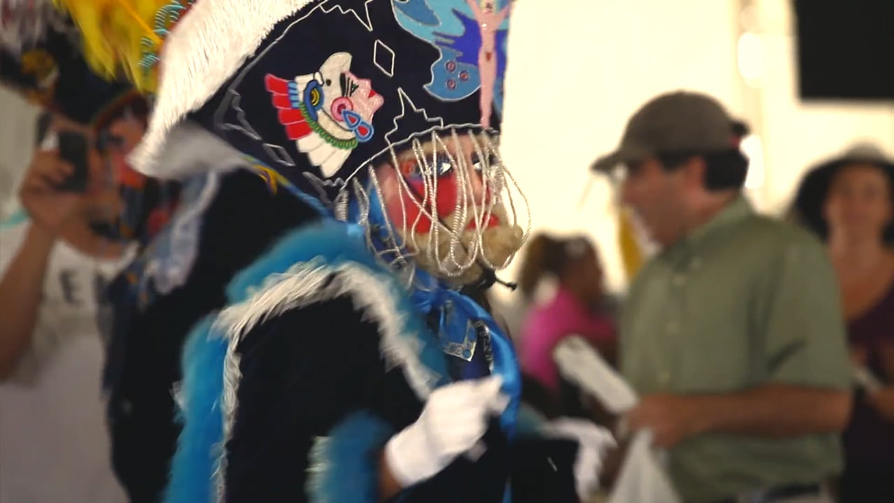 A person in black robe, blue and white feather scarf, decorated hat, and mask dances with a crowd.