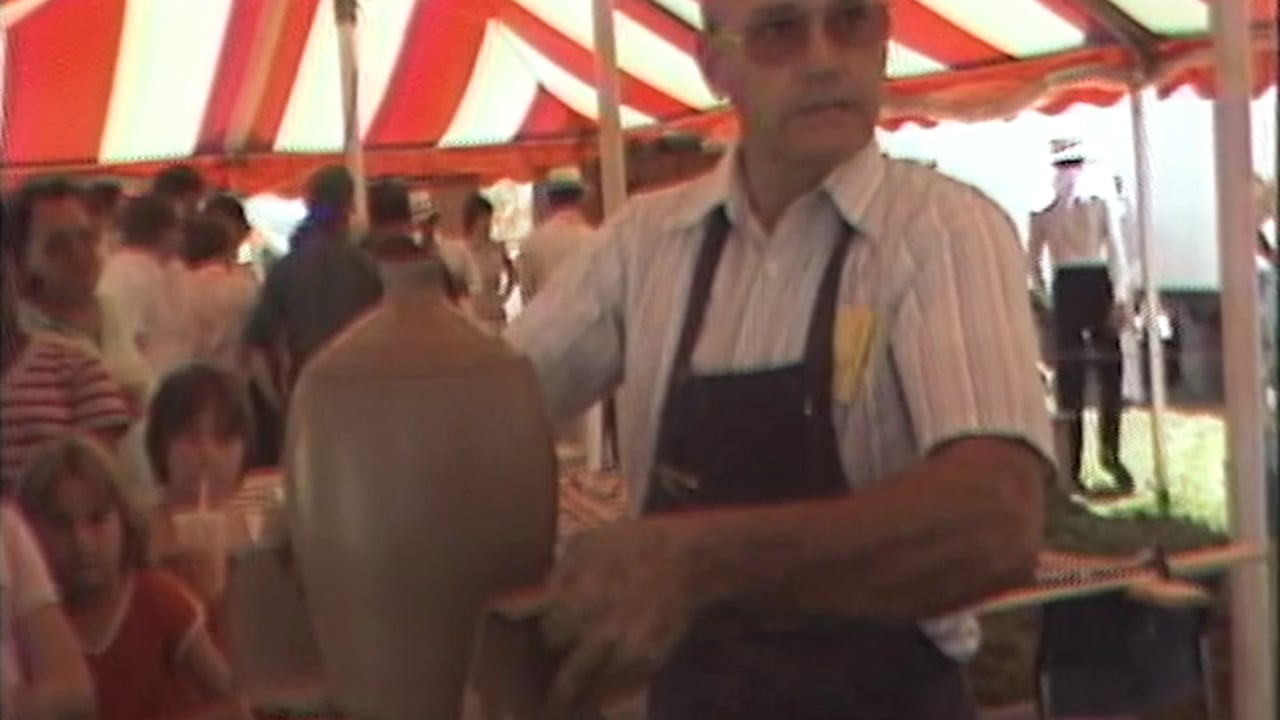 A man holds up an unfinished clay jug for a crowd under a festival tent.