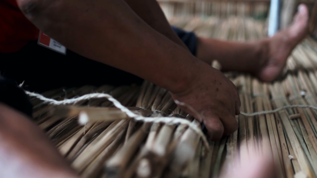 Closeup on the hands and feet of someone sitting on a woven reed mat, stringing pieces together.