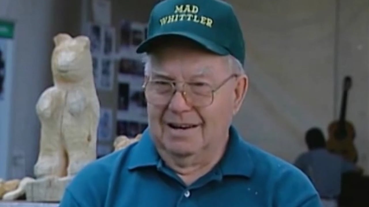 An older man, with a baseball cap that reads MAD WHITTLER, speaks in front of a wooden carving of a bear.