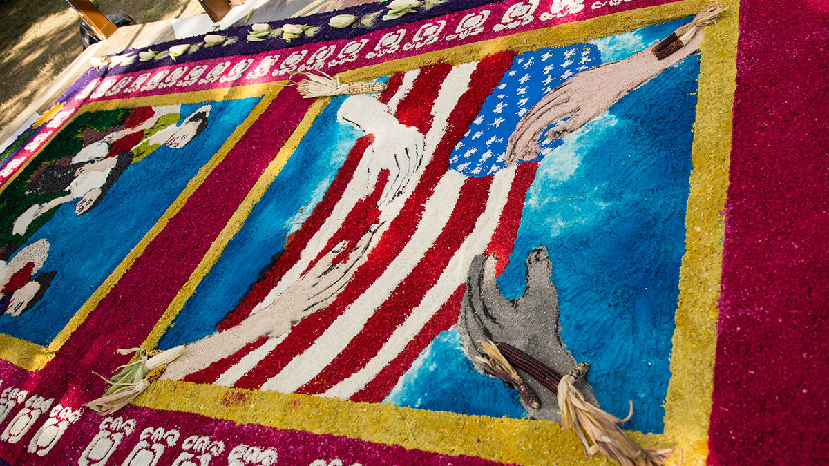 A design made of colored sawdust laid out on the ground, showing four hands of different skin tones around an American flag.
